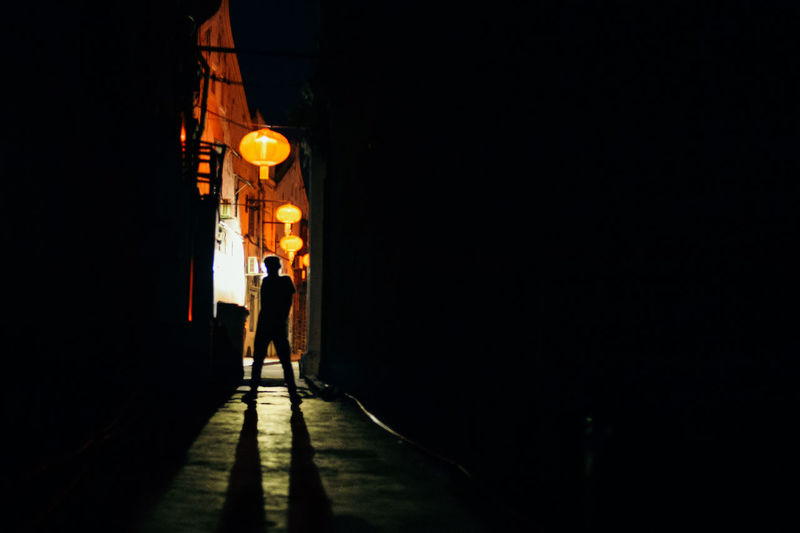 Rear view of a boy silhouette walking on illuminated street at night