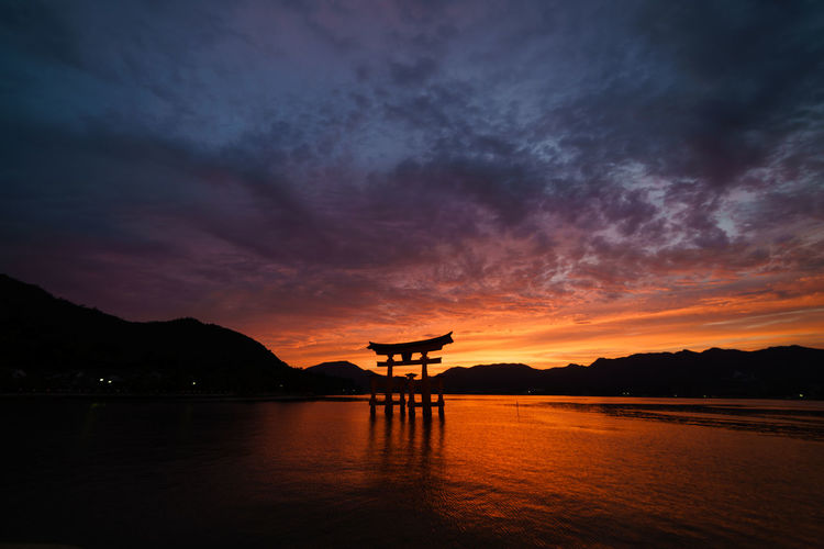 Torii Gate At Itsukushima Shrine Against Cloudy Sky