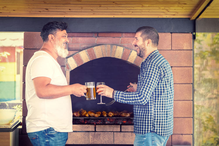 Multiracial male friends cooking meat on barbecue grill while drinking alcohol
