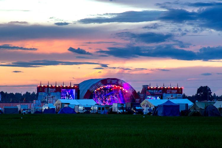 Illuminated ferris wheel on field against sky at sunset