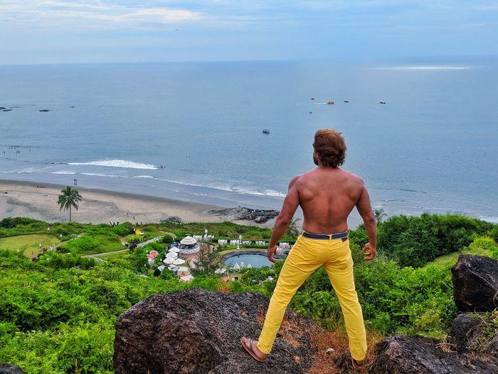 Rear view of shirtless man looking at sea shore