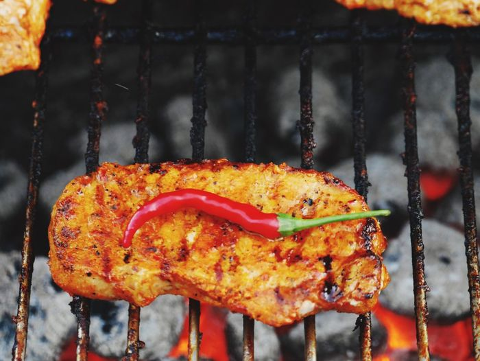 High angle view of meat and red chili pepper on barbecue grill