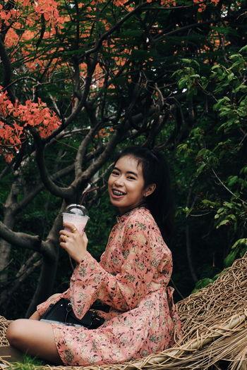 Portrait of smiling woman against plants