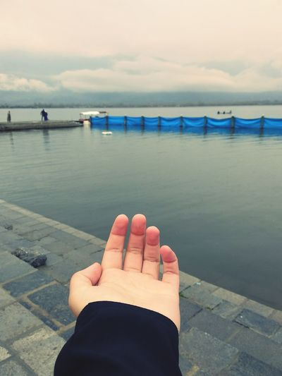 Cropped Hand Gesturing Towards Lake Against Cloudy Sky