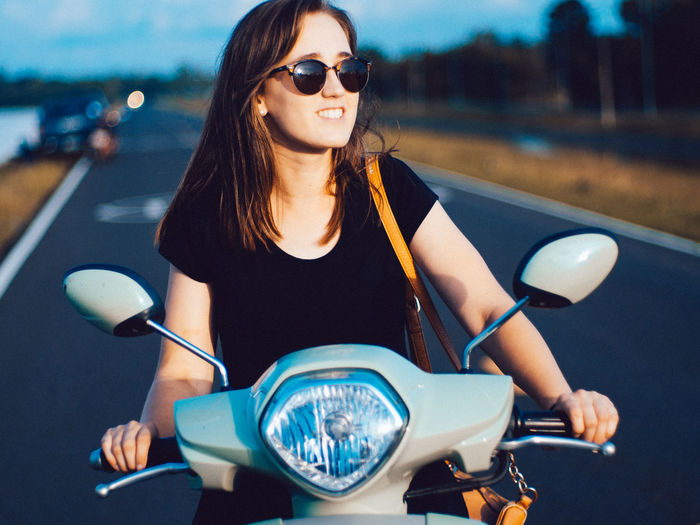 Young woman sitting on motor scooter at road