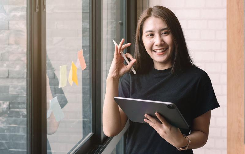 Portrait of smiling young woman using phone while standing on window