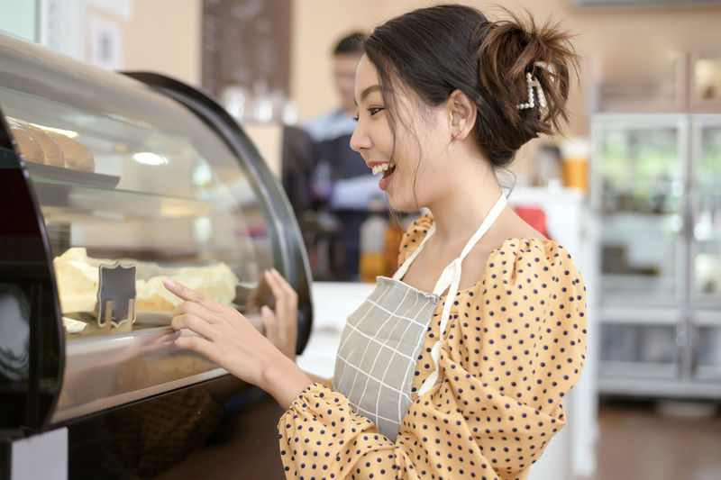 Side view of young woman holding ice cream