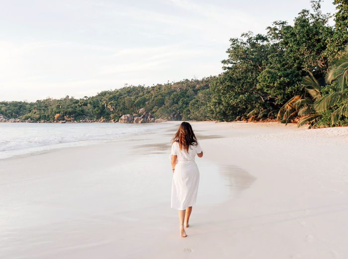 Woman in white summer dress walking on tropical sandy beach.