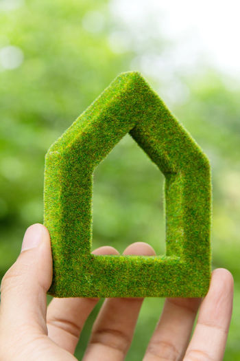 hand holding green house icon concept Eco Green Home Abstract Close-up Concept Conceptual Conceptual Photography  Day Eco Energy Eco Friendly Ecology Focus On Foreground Green Color Home Icon House House Icon Human Body Part Human Finger Human Hand Nature One Person Outdoors People Real People