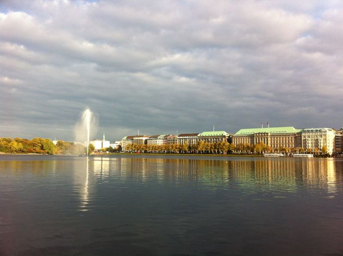Scenic view of alster lake by cityscape against cloudy sky