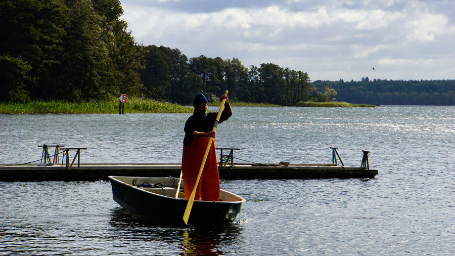 Man standing on boat in lake against sky