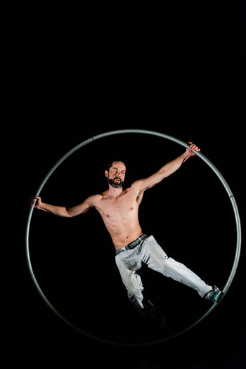 Circus Adult Arms Outstretched Arms Raised Balance Black Background Front View Full Length Human Arm Indoors  Limb Males  Men One Person Performance Shirtless Skill  Sport Studio Shot Vitality Young Adult