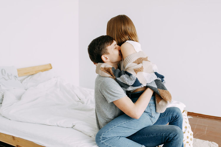 Home love story, guy and girl hug and kiss in the bedroom of the house