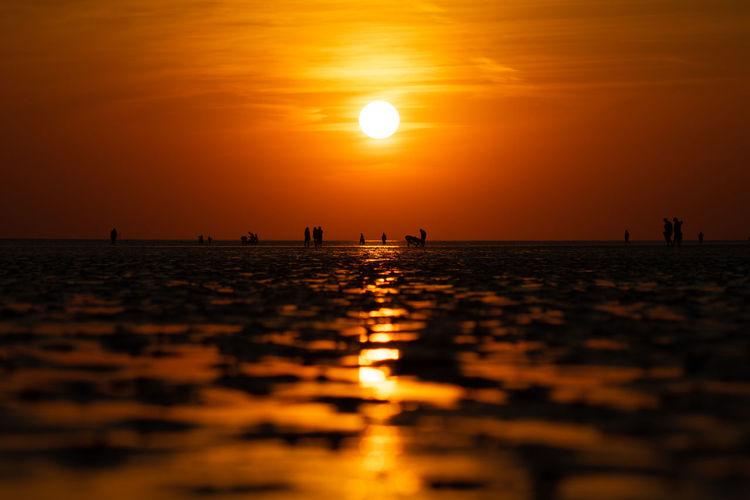 Silhouette people on sea against orange sky