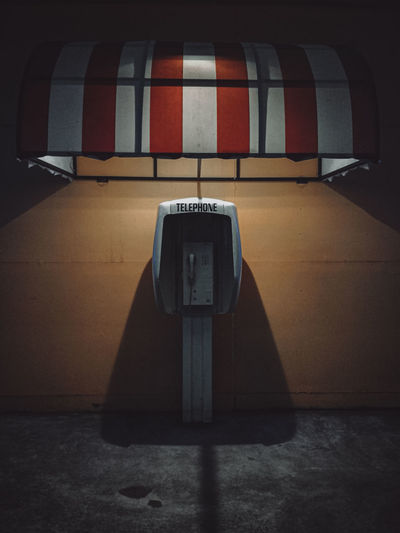 High angle view of telephone booth on floor against wall