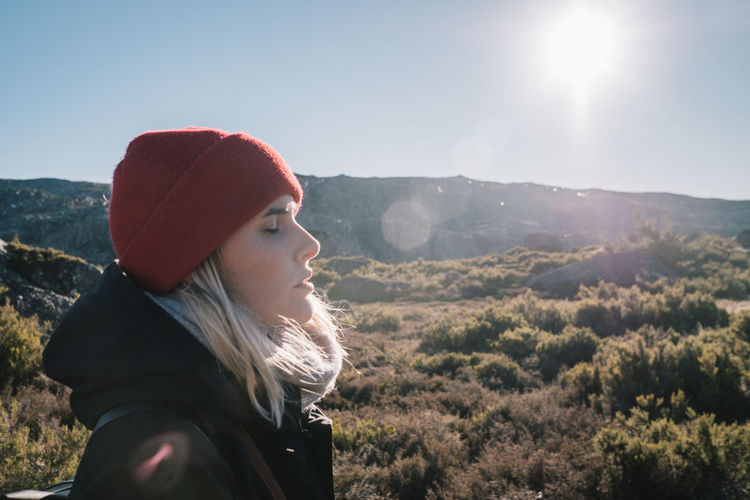 Side view of young woman standing on mountain against sky