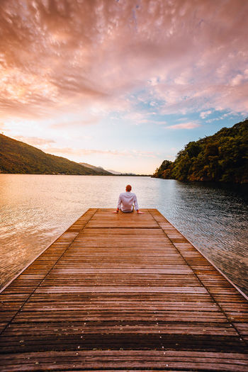 Man sitting on pier over lake against sky during sunset