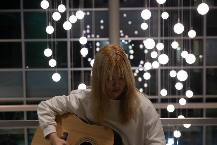 Young woman playing guitar illuminated lights