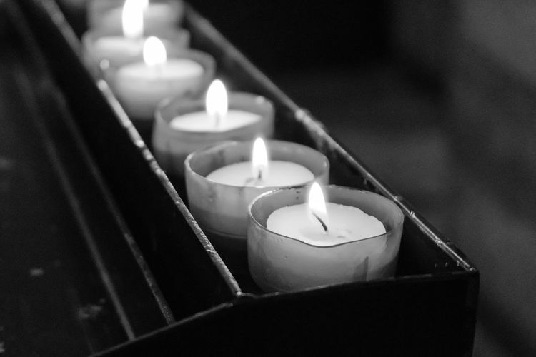 Close-up of candles on votive stand in church
