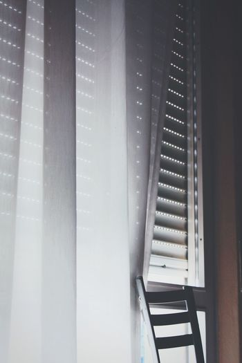 Cropped Image Of Chair By Window Curtain At Home