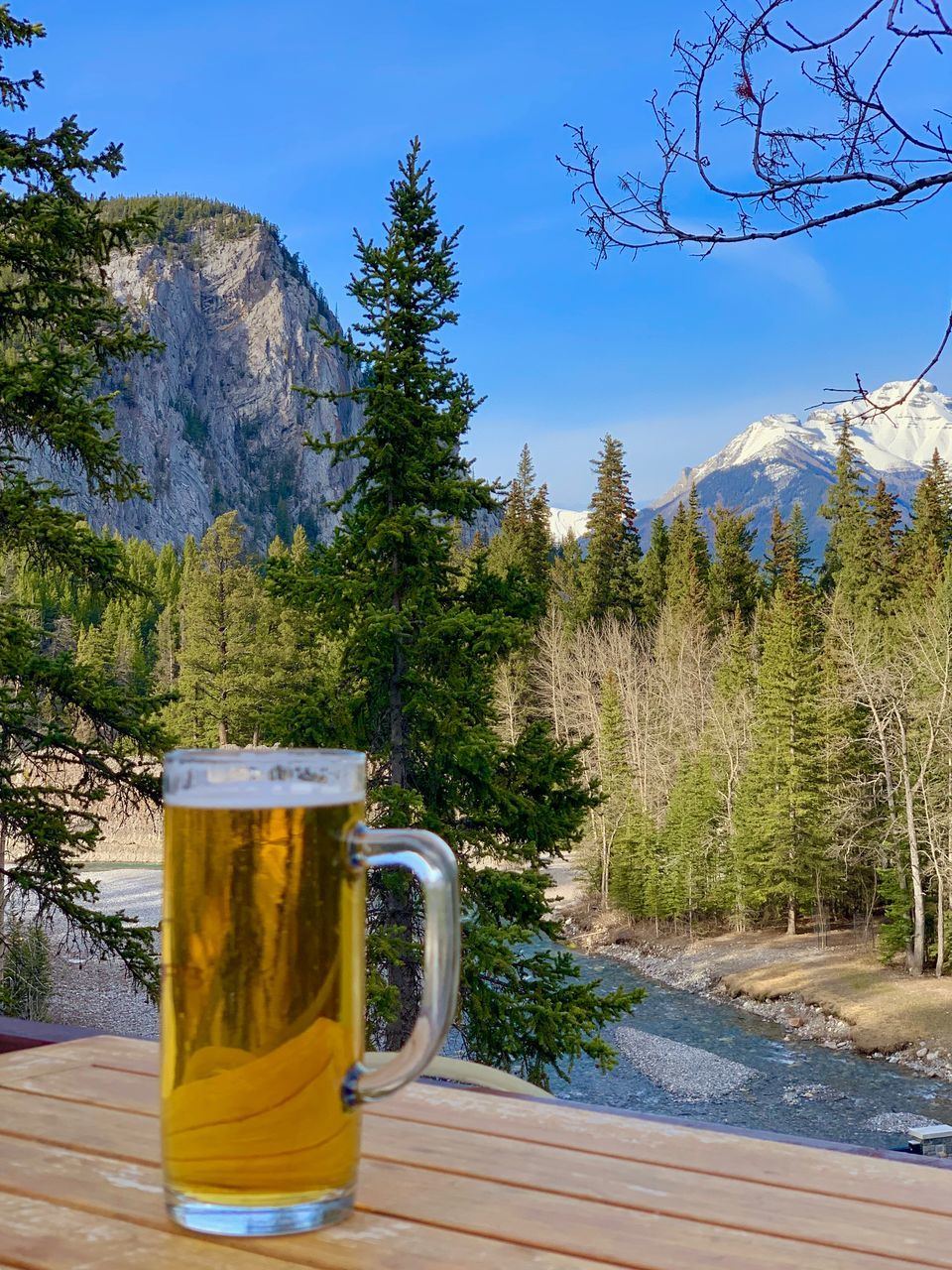 BEER GLASS ON TABLE AGAINST MOUNTAINS