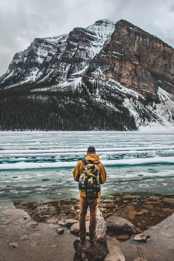 Rear View Of Man With Backpack Standing On Rock By Lake Against Mountain During Winter