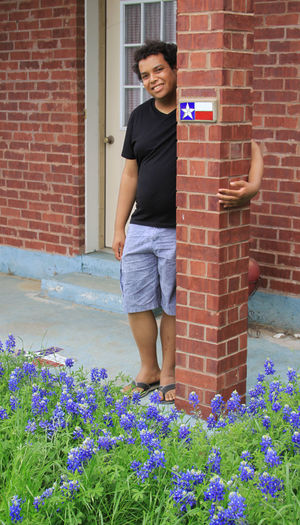 Architecture Brick Brick Wall Building Exterior Built Structure Casual Clothing Child Day Flower Flowering Plant Front View Full Length Leisure Activity Lifestyles One Person Outdoors Plant Real People Standing Teenager Wall