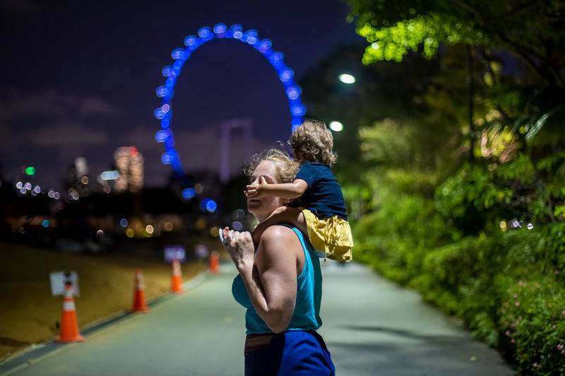 Mother carrying daughter against illuminated ferris wheel