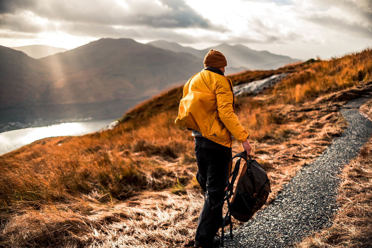 Rear view of man hiking on mountain during sunset