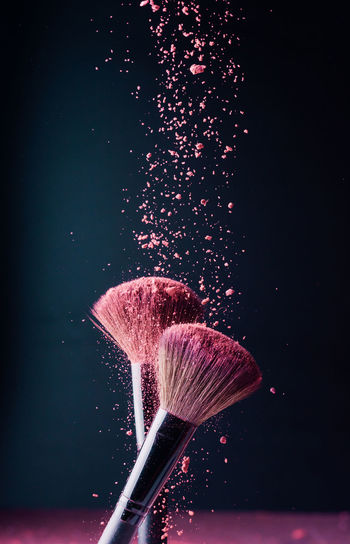 Close-up of pink umbrella against black background