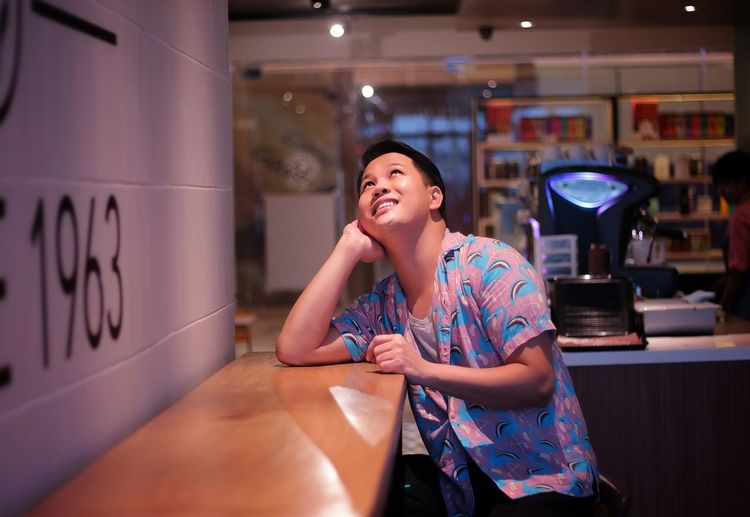 Smiling Man Looking Up While Sitting On Table At Cafe