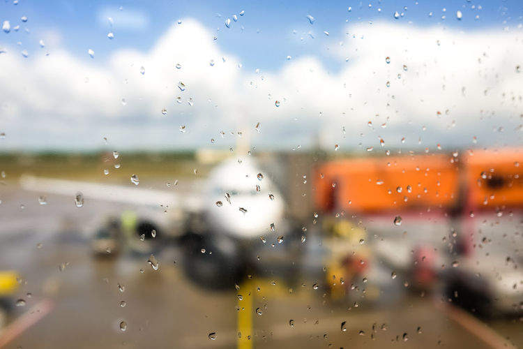 Aircraft Airplane Airport At The Airport Backgrounds Blurred Cloud - Sky Copy Space Drop Droplet Finger Flight Glass - Material Loading Mode Of Transport Parking Parking Position Plane Rain Starting A Trip Transportation Traveling Weather Wet Window