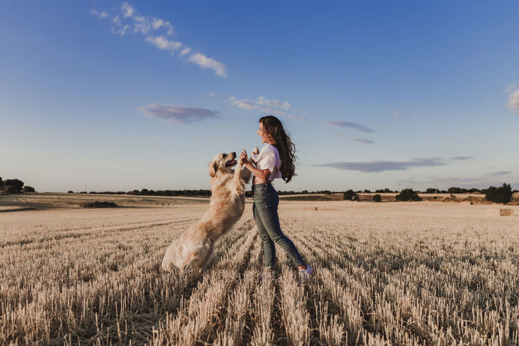 Mid adult woman with dog on agricultural field