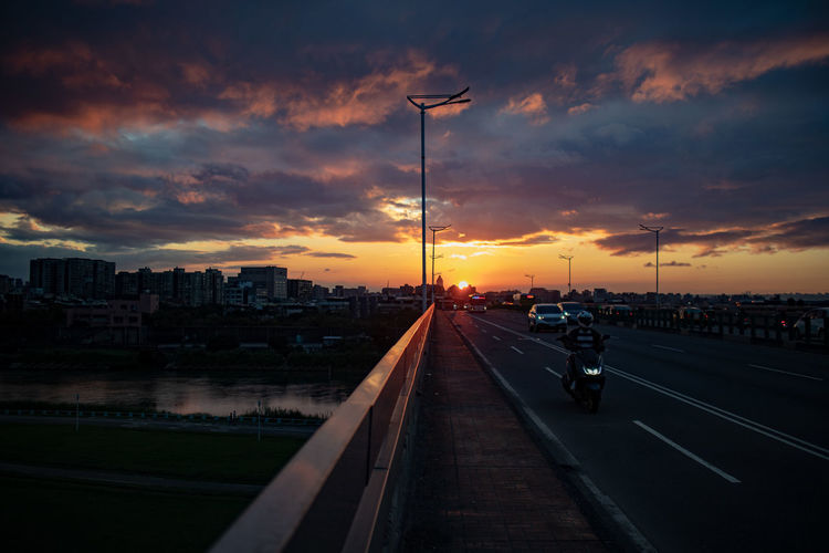 Sky Sunset Cloud - Sky Architecture Transportation City Building Exterior Built Structure Street Nature Road Mode Of Transportation Orange Color Land Vehicle Street Light No People Outdoors Car Lighting Equipment Motor Vehicle Cityscape Track