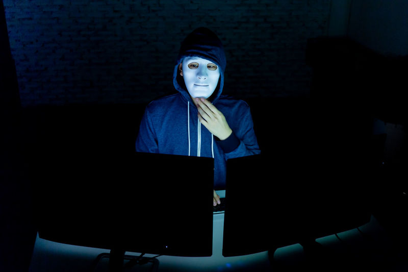 Masked hacker under hood using computer to hack into system and trying to commit computer crime - Hacker and computer threat crime concept Crime Attack Black Cyberspace Danger Dark Data Security Hacker Hide Identity Indoors  Internet Lifestyles Masked Network One Person Online  Password Portrait Programmer Real People Safety Steal Thief Waist Up