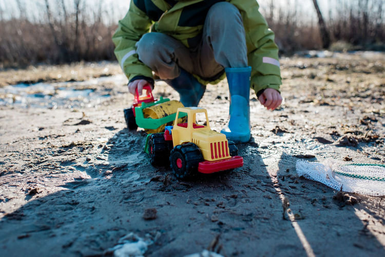 Low section of boy playing with toy on land