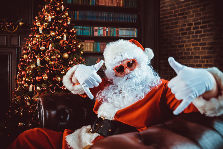 Portrait of man in santa claus costume gesturing while sitting by christmas tree at home