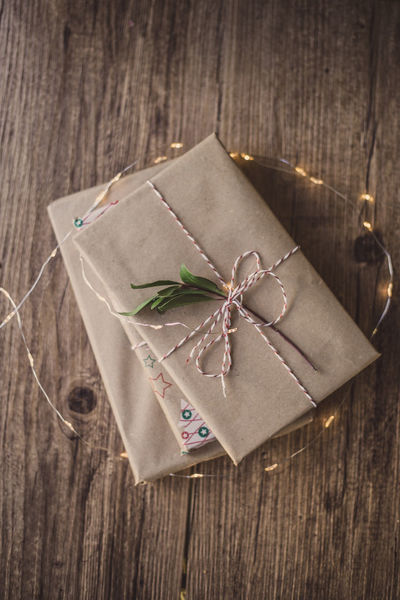Wrapped gifts on wooden table Book Birthday Christmas Holiday Love Wrap Chritsmas Decoration Gift Paper Wrapped Wood - Material Wrapping Paper Christmas Present Celebration High Angle View Indoors  No People Close-up Tied Up Studio Shot Day Ribbon - Sewing Item Brown Paper Rustic Tying
