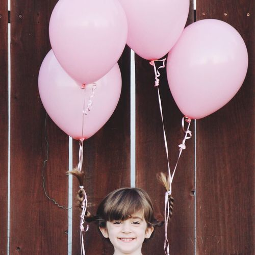 Close-up of smiling girl hanging on balloons