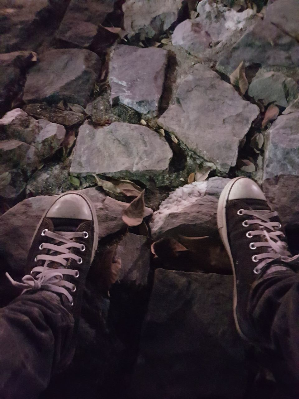 low section, shoe, human leg, body part, human body part, personal perspective, one person, real people, lifestyles, men, day, rock, human foot, high angle view, leisure activity, solid, standing, outdoors, rock - object, human limb, jeans