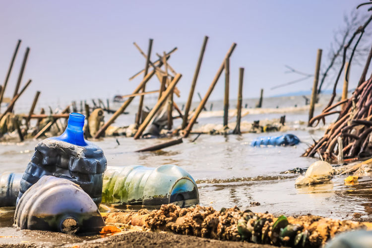 Close-up of abandoned bottle on beach against sky