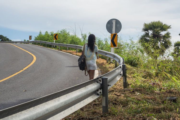 Rear view of woman on road against sky