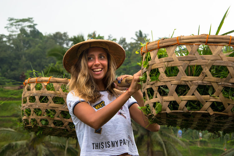 Smiling Woman Holding Basket Against Sky