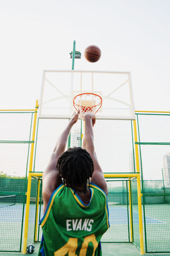 Low angle view of boy playing basketball hoop