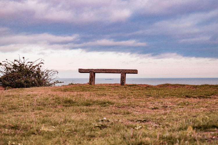 container ship under a bench on a cliff Container Ship Northsea Cliff Bench Wooden Bench Underneath Alignment Perfect Alignement Dark Clouds Seat Grass Focus On Background Sky Grass Landscape Shore Idyllic Horizon Over Water Non-urban Scene Ocean Coast Scenics Tranquility Calm Tranquil Scene Remote