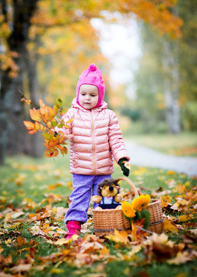 Full Length Of Cute Girl With Autumn Leaves