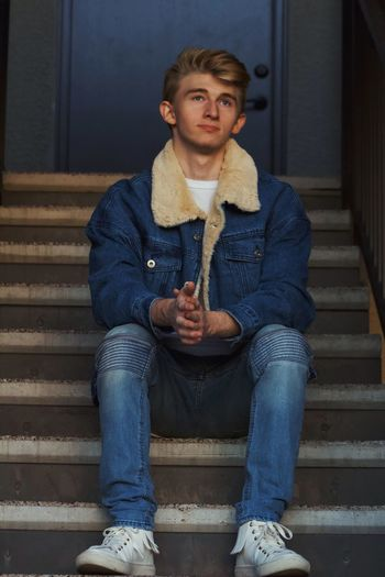 Full length of thoughtful young man looking away while sitting on staircase