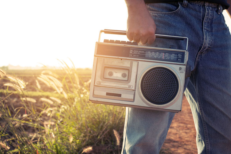 Man hand holding vintage radio on nature background Listening To Music Man Music Radio Rustic Vintage Style Adult Countryside Day Field Holding Human Hand Lifestyles Low Section Men Nature News One Man Only One Person Outdoors People Photography Themes Rural Scene Sky Standing