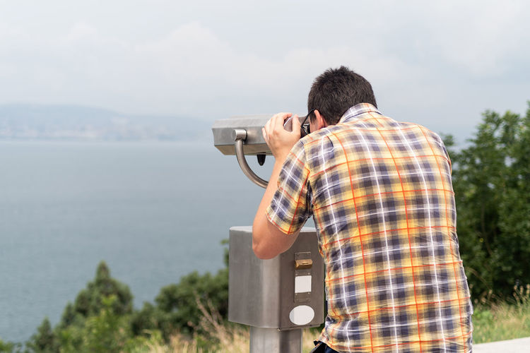 Man using stationary binoculars  on a hill against the background of the mountains and sea