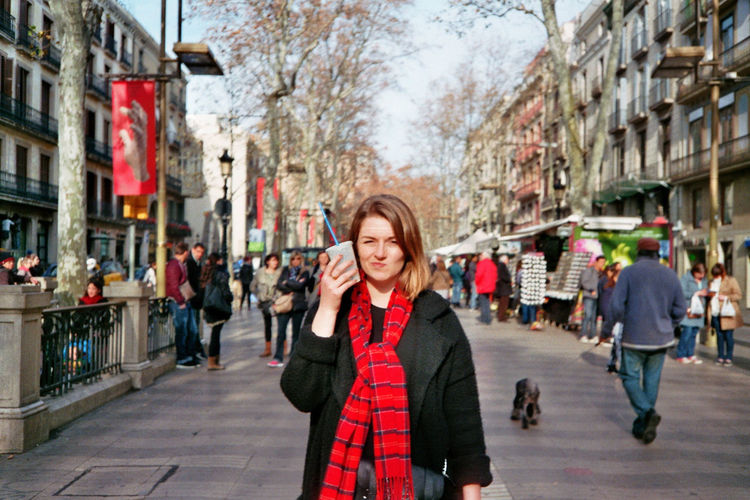 Portrait of woman holding disposable glass on street in city
